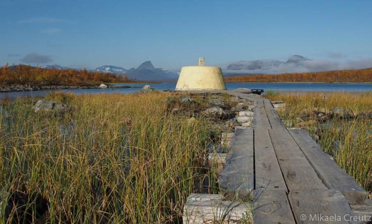 Kolmen valtakunnan rajapyykki. Taustalla Norjan tunturit, terävä huippu on Bárrás.