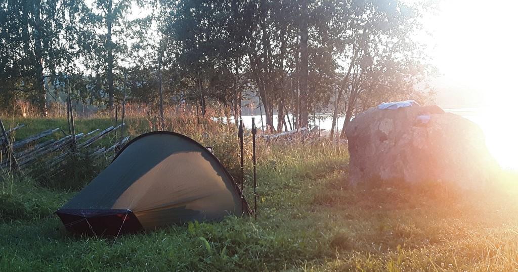 Teltta pystytetty Lakkalan nurmelle kohti Herajärveä ja auringonlaskua.